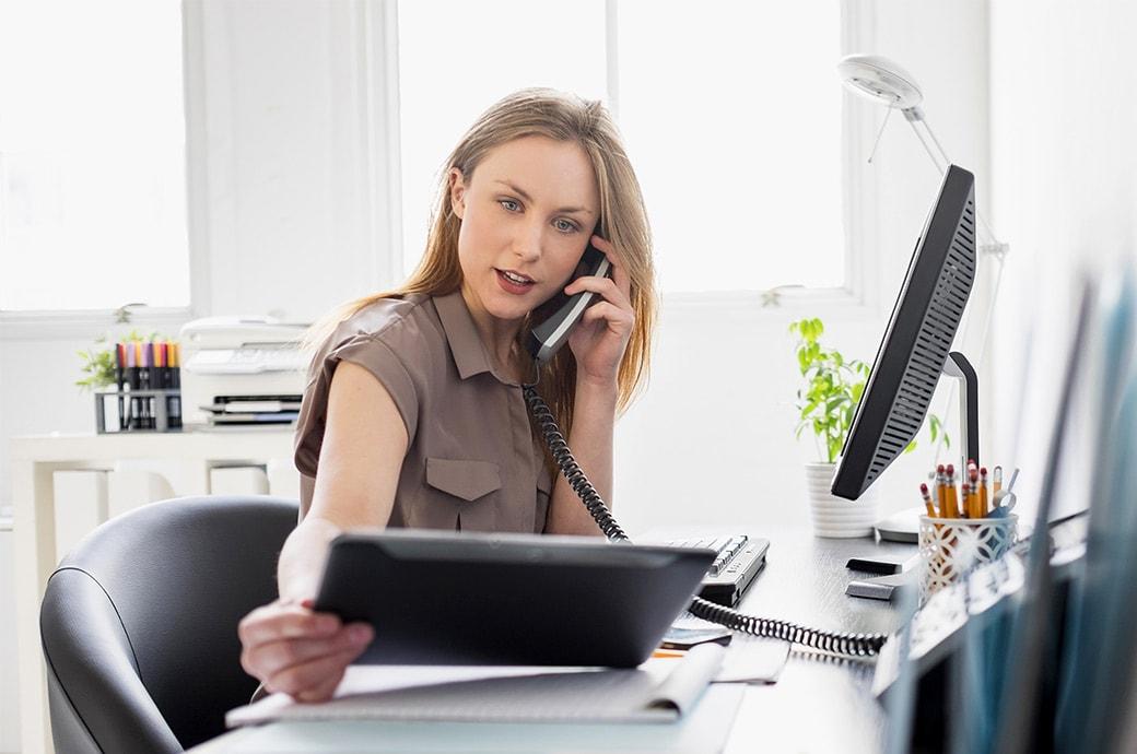 Kobieta pracująca przy biurku, rozmawiająca przez telefon i patrząca w tablet