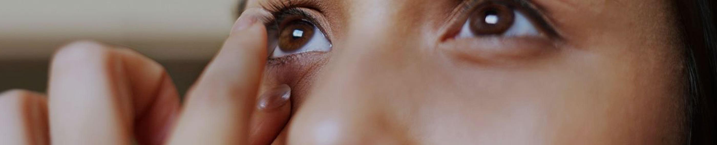 Wpatrzona w lustro kobieta zakładająca soczewki kontaktowe