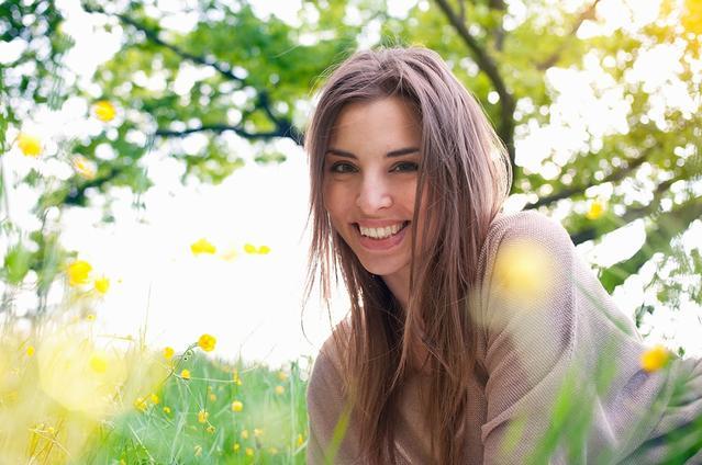 Uśmiechnięta dziewczyna siedząca koło drzewa na łące