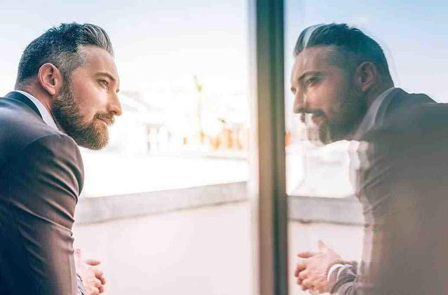 Dojrzały mężczyzna zerkający na swoje odbicie w oknie