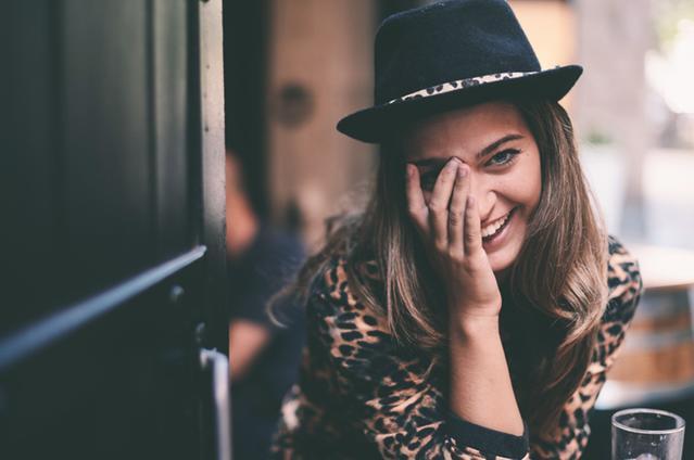 Dziewczyna z ręka przy oku stojąca przy drzwiach