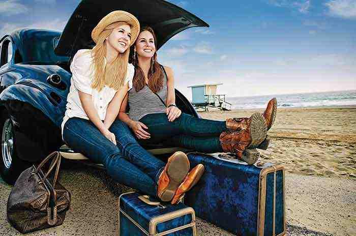 Dwie dziewczyny na wakacjach na plaży siedzące na samochodzie otoczone przez bagaż