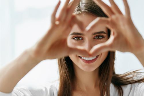 Uśmiechnięta dziewczyna układająca dłonie przy oczach w kształt serca