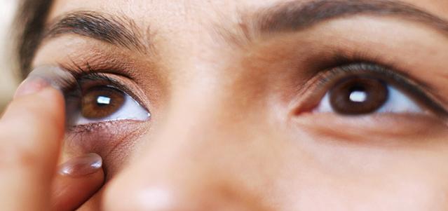 Zbliżenie na oczy dziewczyny, która zakłada soczewkę kontaktową