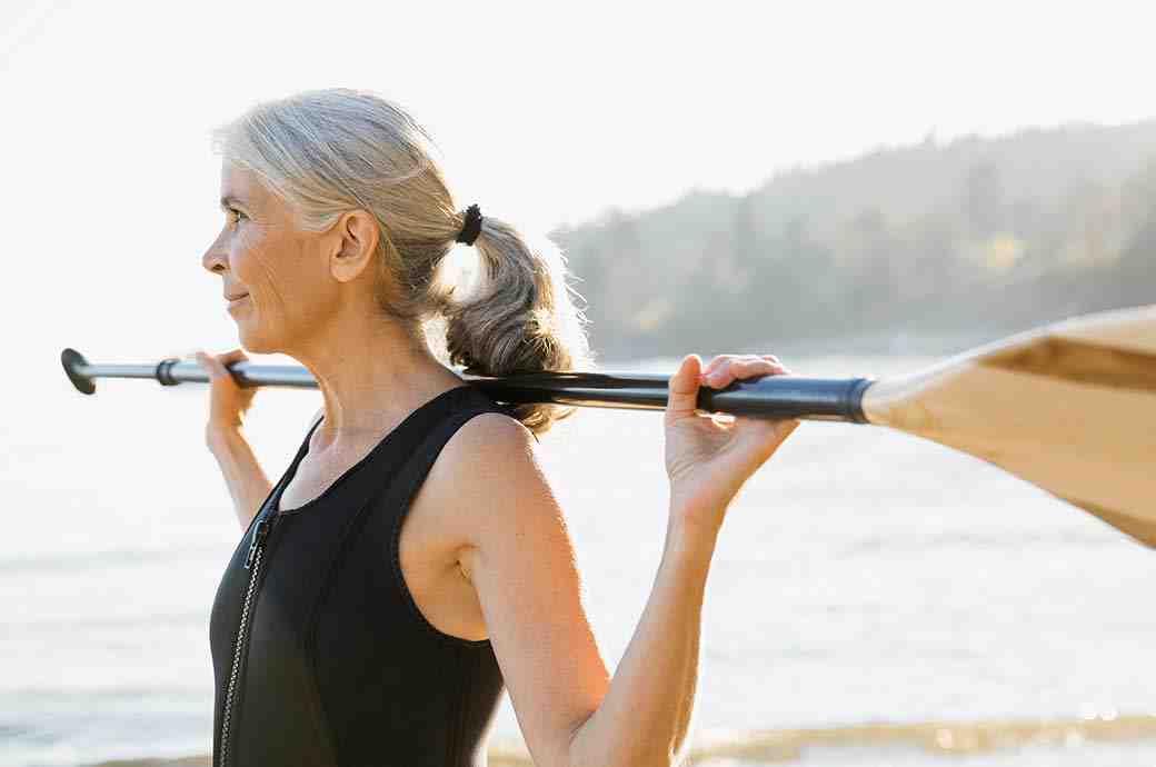 Dojrzała kobieta nad jeziorem trzymająca wiosło
