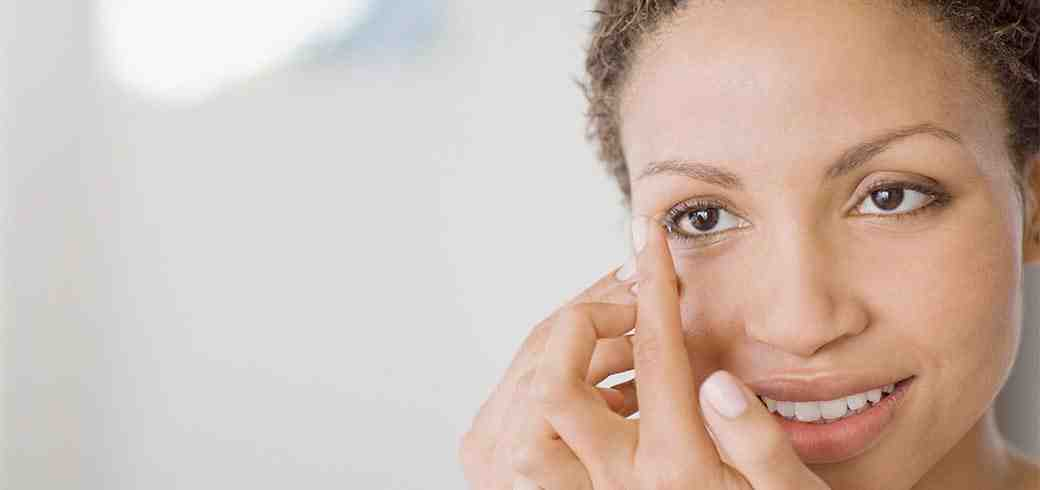 Kobieta zakładająca soczewkę kontaktową