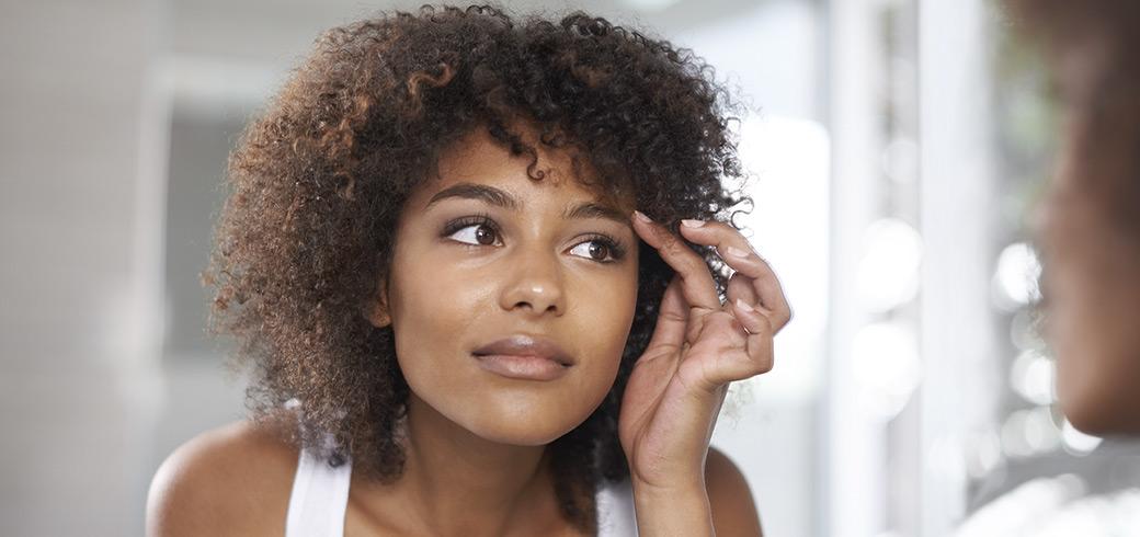 Młoda kobieta spoglądająca na swoje oczy w lustrze